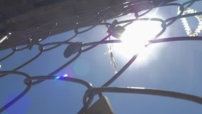 A closeup of a metal mesh fence with symbolic locks on it. The is a bright sun on a blue sky behind it stock video