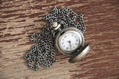 Closeup of metal vintage open pocket clock with chain on brown o royalty free stock image