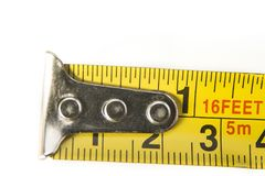 Closeup of meter tape in centimeters and inches on the white background. Closeup of meter tape in centimeters and inches on the white background royalty free stock photo