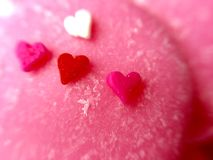 Closeup Micro Heart Sprinkles. Colorful micro heart sprinkles on pink chocolate candy melts Royalty Free Stock Image