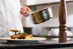 Closeup mid section of a chef garnishing food Stock Images
