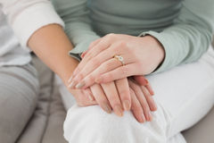 Closeup mid section of female friends touching hands Stock Image