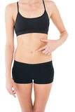 Closeup mid section of a fit woman with hand on stomach Royalty Free Stock Images