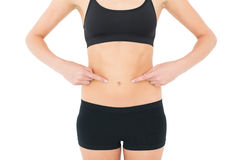 Closeup mid section of a fit woman with hands on stomach Royalty Free Stock Photo