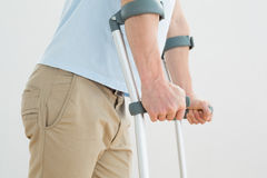 Closeup mid section of a man with crutches Royalty Free Stock Photo