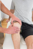 Closeup mid section of a man getting his knee examined Stock Images