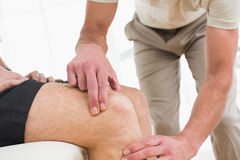 Closeup mid section of a man getting his knee examined Royalty Free Stock Image