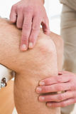 Closeup mid section of a man getting his knee examined Royalty Free Stock Images