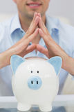Closeup mid section man with piggy bank at home Stock Image