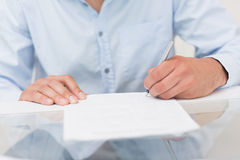 Closeup mid section of a man writing documents Stock Photos