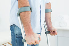 Closeup mid section of a young man with crutches Stock Images
