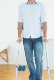 Closeup mid section of a young man with crutches Royalty Free Stock Image