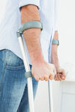 Closeup mid section of a young man with crutches. Standing in the medical office Royalty Free Stock Photography