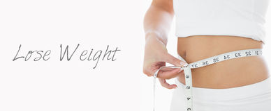 Closeup midsection of woman measuring waist Royalty Free Stock Photo