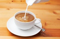 Closeup of milk and coffee. Closeup of coffee with milk being poured into the cup.  Shot on light wood background Stock Photography