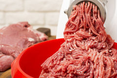 Closeup of minced meat coming out from grinder. Stock Photo