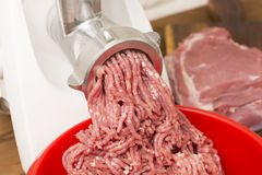 Closeup of minced meat coming out from grinder. Royalty Free Stock Images