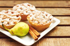 Closeup of mini pies on a plate decorated with cinnamon and a pear Stock Photos