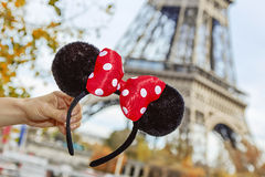 Closeup on Minnie Mouse Ears in hand in front of Eiffel tower. Perfect autumn holidays in Disneyland and Paris. Closeup on Minnie Mouse Ears in female hand on royalty free stock images