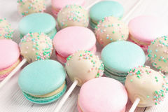 Closeup of mint and strawberry flavor macarons and cake pops. Closeup set of mint and strawberry flavor macaroons and cake pops on sticks Royalty Free Stock Image