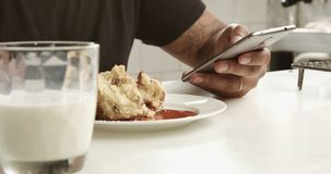Closeup of mixed race man`s hand texting in smartphone during breakfast. With milk on a first plane stock footage