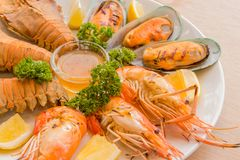 Closeup Mixed Seafood On Plate. Mixed Seafood Contain Big Shrimps, Grilled with Sauce and Lemon on Dish, Isolated on Wood background Stock Photos