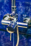 Closeup of mixer bathroom, background blue terracotta tiles Royalty Free Stock Photography