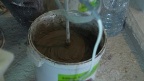 Closeup of mixing adhesive solution in bucket at construction site. Worker preparing mixture for brick laying. home renovation, construction and hard work stock footage