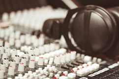 Closeup mixing console with headphones on top, faders and knobs background, artistic studio equipment concept Royalty Free Stock Photos
