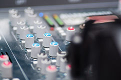 Closeup mixing console with headphones on top, faders and knobs background, artistic studio equipment concept Stock Photos
