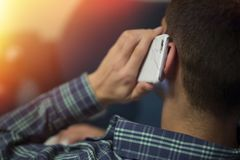 Closeup mobile phone in the ear listening. And talking royalty free stock photo