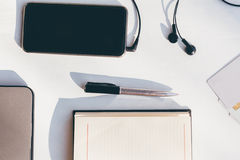 Closeup of mobile phone with headphones, pen, notes, laptop and Royalty Free Stock Photo
