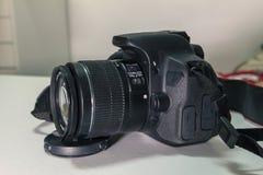 Closeup of modern black DSLR camera on white table.  Stock Images