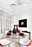 Closeup of a modern dining area with a glass table and chairs. Dining room of a luxurious house, chairs are curved and in red. The round table is made of glass royalty free stock image
