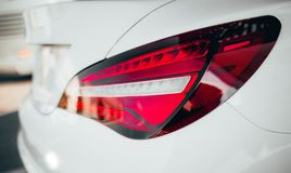Closeup modern luxury grayBack lights headlight and head lamp of powerful beast sport car . Dealership office showroom for sale ba. Ckground hype epic toned royalty free stock images