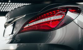 Closeup modern luxury grayBack lights headlight and head lamp of powerful beast sport car . Dealership office showroom for sale ba. Ckground hype epic toned royalty free stock photo