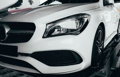 Closeup modern luxury white front lights headlight and head lamp rims of powerful sport car. Dealership office showroom sale hype. Epic toned wallpaper. Tuning royalty free stock photography