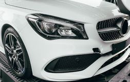 Closeup modern luxury white front lights headlight and head lamp rims of powerful sport car. Dealership office showroom sale hype. Epic toned wallpaper. Tuning stock image