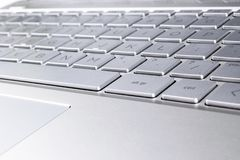 Closeup of a modern silver laptop computer keyboard. Laptop keyboard. Detail of the new and ergonomic computer keyboard.  royalty free stock images