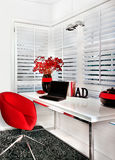 Closeup of a modern work room with a red chair a white table inc Royalty Free Stock Image
