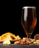 Closeup of moist glass of brown ale, with crisps, bacon, peanuts, hazelnuts, and pistachios on a dark background. Snacks. A moist glass of brown ale, with royalty free stock photography