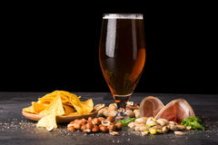 Closeup of moist glass of brown ale, with crisps, bacon, peanuts, hazelnuts, and pistachios on a dark background. Snacks. A moist glass of brown ale, with stock photo
