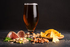 Closeup of moist glass of brown ale, with crisps, bacon, peanuts, hazelnuts, and pistachios on a dark background. Snacks. A moist glass of brown ale, with stock photos