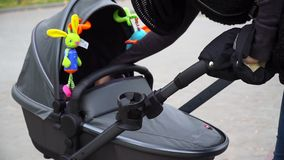Closeup mom shakes stroller with a child stock video footage