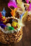 Closeup of a mona de pascua, a cake eaten in Spain on Easter Monday, ornamented with feathers and a teddy chick on on a rustic stock photos
