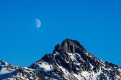 Closeup of moon rising over the mountain peak. Moon rising over the scenic mountain range near garibaldi lake, Canada, BC royalty free stock photo