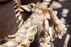 Closeup of a mooring rope with a knotted end tied around a cleat Royalty Free Stock Images
