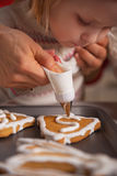 Closeup on mother and baby decorating cookies with glaze Royalty Free Stock Photography