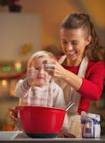 Closeup on mother and baby hand pouring flour into bowl Royalty Free Stock Images