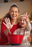 Closeup on mother and baby hands smeared in flour Royalty Free Stock Photos